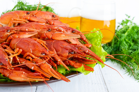 A large pile of boiled crawfish on a ceramic plate,  glasses of beer on a white wooden background. Close up