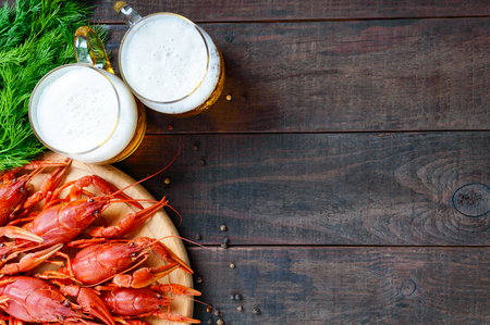 A  pile of tasty boiled crawfish on a round wooden tray and two mugs of cold beer on a dark background. Top view. Free space for an inscription.