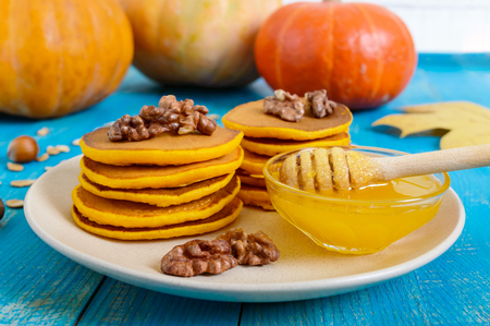 Fragrant golden pumpkin pancakes with honey and walnuts on a blue wooden background. Traditional American dish Stock Photo