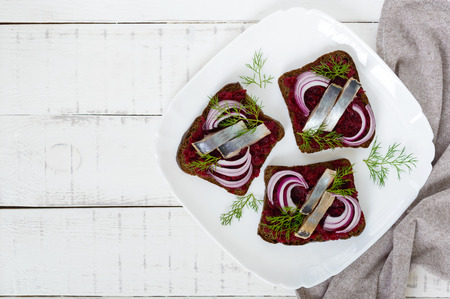 Dietary sandwiches with herring, boiled beets, red onion on rye bread on a white wooden background. Top view.