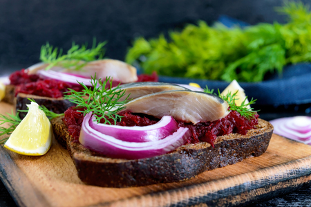 Dietary sandwiches with beets, slices of salted herring and red onion on rye bread on a black background.