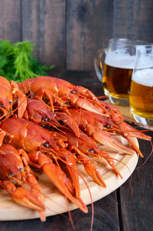 A pile of large crawfish on a wooden tray, glasses with beer on a dark wooden background.