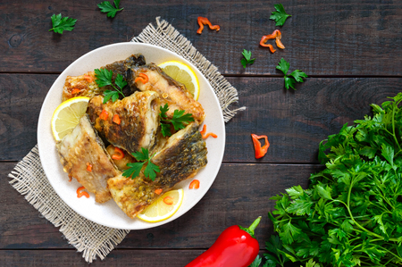 Pieces of roasted carp with lemon and greens on a plate on a dark wooden background. Top view. Фото со стока - 91389169