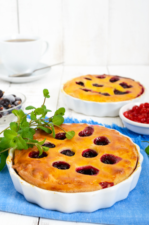 Tasty homemade berry pies in a round ceramic form on a white wooden background.