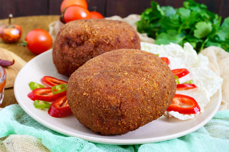 Juicy golden cutlets stuffed with boiled egg on a wooden background. Stock Photo