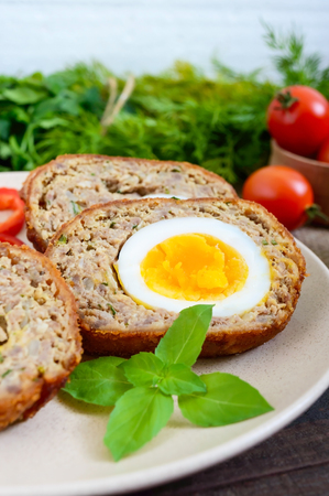 Meat cutlet with boiled egg, pieces on a ceramic plate on a dark wooden background. Mini meat rolls. Scottish cutlet. Stock Photo