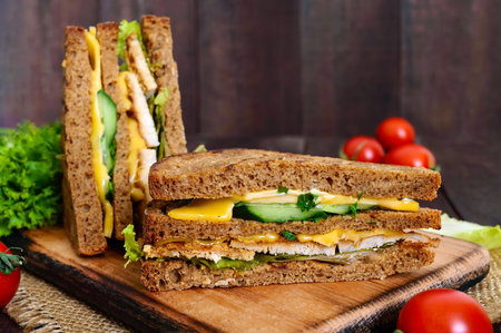 Delicious club-sandwich with rye bread, chicken, cheese, cucumbers, greens on a dark wooden background.