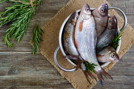 A pile of fresh raw fish on a wooden background. Top view. Carp. Fresh catch.