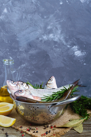 A pile of fresh raw fish with spices, lemon, rosemary on a wooden background. Fresh catch. Vertical view