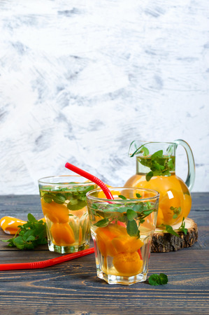 Summer cold drinks. Delicious refreshing drink with apricot and mint in glasses on a wooden table. Compote of fruits. Selective focus. Stock Photo