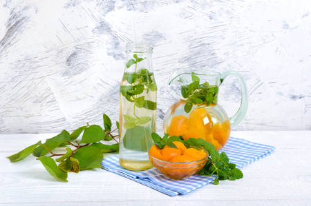 Summer cold drinks. Delicious refreshing drink with apricot and mint in glasses on a white wooden background. Compote of fruits.