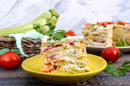 A piece of delicious cake of zucchini, tomatoes and cheese on a wooden table. Vegetable cake.