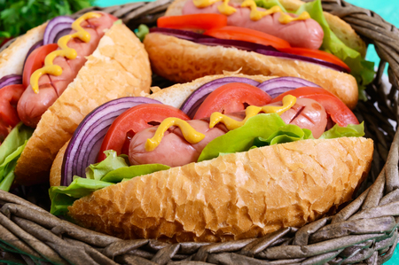 Delicious hot dog in a basket on a bright background. Grilled sausage with tomatoes, red onions, lettuce, mustard in a crispy loaf. Street food. Fast food.