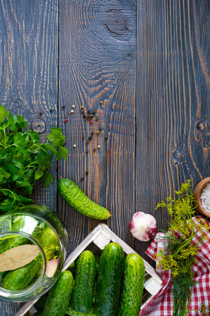 Pickles. Delicious pickled cucumbers in a jar, fresh harvest in a wooden box, spices, herbs on a table. Preparation of cucumbers for pickles. Top view.