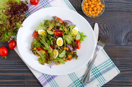 Dietary, vegetarian salad with quail eggs, fresh herbs, chickpeas, red onions and cherry tomatoes.