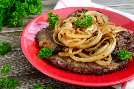 Juicy slices of fried liver and onions on a red plate.