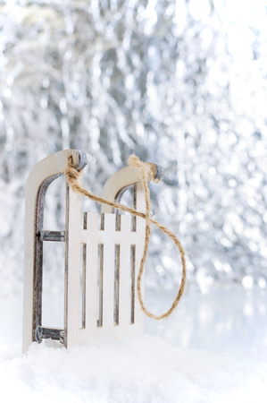 New Year, Christmas greeting card. Small decorative wooden toy sleds on the snow. Bokeh. Christmas background.