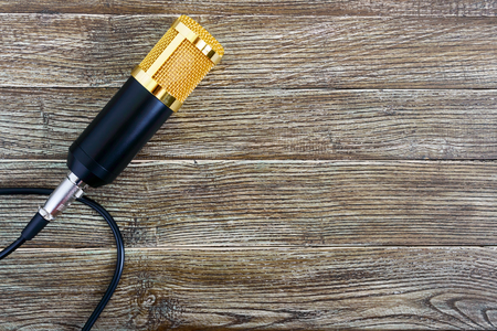 Condenser gold microphone with cable on a wooden table with copy space. Musical theme. Flat lay. Top view. Banque d'images - 116532953