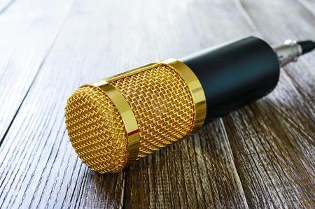 Condenser gold microphone  on a wooden table. The light from left side. Musical theme. Banque d'images - 116532967