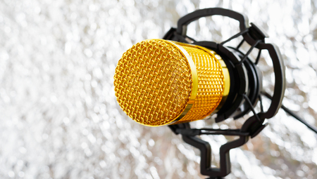 Beautiful golden microphone on a light blurred background, close up, bokeh. Banque d'images - 116533082