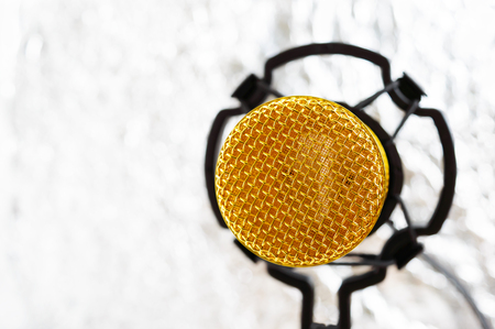 Beautiful golden microphone on a light blurred background, close up, bokeh.