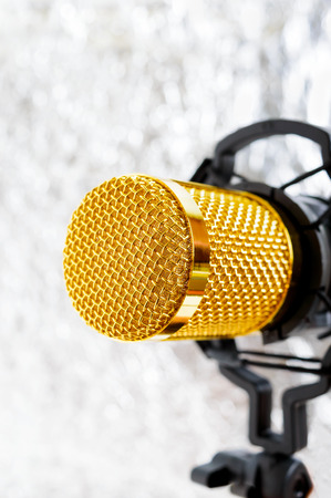 Beautiful golden microphone on a light blurred background, close up, bokeh. Banque d'images - 116533138