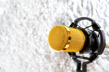 Beautiful golden microphone on a light blurred background, close up, bokeh. Banque d'images - 116533140