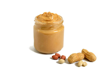 Peanut butter in a glass jar with peanuts isolated on white background.  A traditional product of American cuisine. Фото со стока