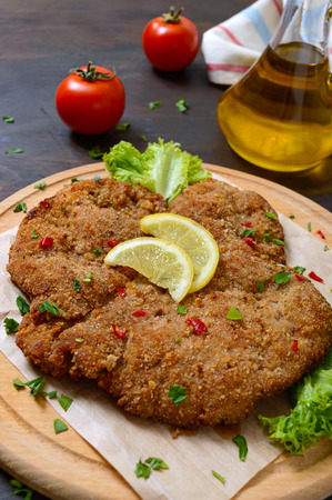 Large Viennese schnitzel on a wooden board with lemon on a dark background. Meat dish 版權商用圖片