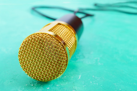 Beautiful golden microphone on a bright background, copy space, close up, bokeh. Banque d'images - 117843311