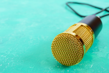 Beautiful golden microphone on a bright background, copy space, close up, bokeh.