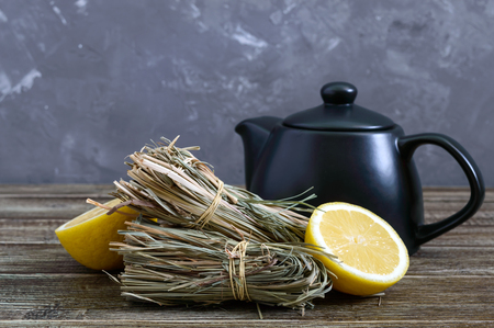 Organic dry lemongrass (Cymbopogon flexuosus) in bunches and lemon fruit on a wooden table. Herbs for tea.