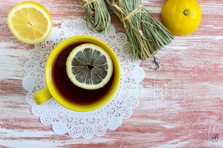 A bunch of dry lemongrass, fresh lemon and a cup of tea. Tea Ingredients. The culture of tea drinking. Top view. Flat lay.