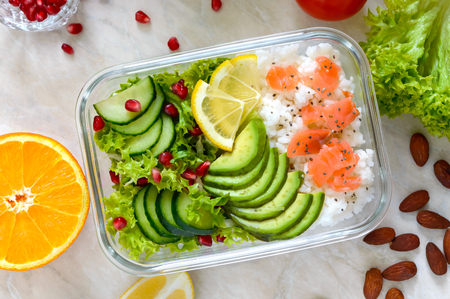 Lunch box: rice, salmon, salad with cucumber, avocado, greens. Fitness food. The concept of healthy eating. School lunch box