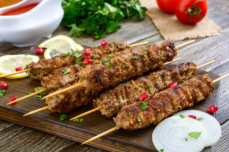 Delicious lula kebab on a wooden table. Chopped meat on wooden skewers, grilled. Eastern cuisine.