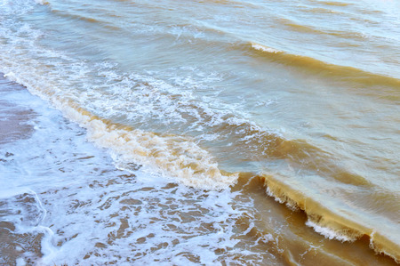Waves on the shore. Sea wave close up on a sandy beach with sunlight. Archivio Fotografico