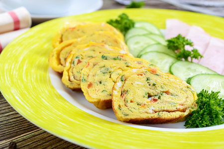 Omelette, egg roll with ham and fresh cucumber on a wooden table. Tasty healthy breakfast. Reklamní fotografie