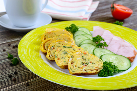 Omelette, egg roll with ham and fresh cucumber on a wooden table. Tasty healthy breakfast. Reklamní fotografie - 122936285