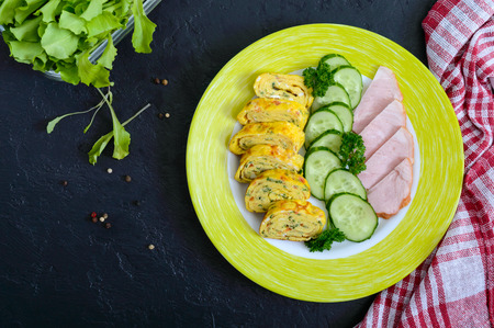 Omelette, egg roll with ham and fresh cucumber on a black background. Tasty healthy breakfast. The top view, flat lay