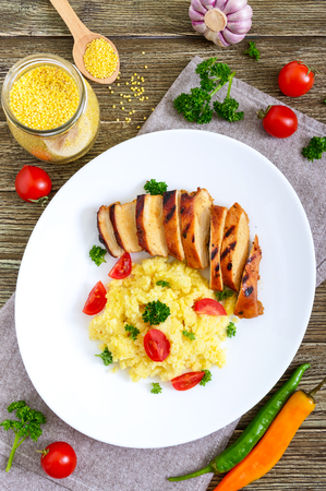 Grilled chicken breast and delicious millet porridge on a white plate on a wooden table. Top view Фото со стока
