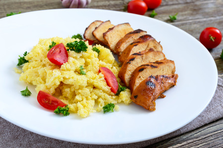 Grilled chicken breast and delicious millet porridge on a white plate on a wooden table