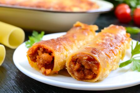 Stuffed cannelloni with bechamel sauce. Cannelloni pasta baked with meat, cream sauce, cheese on a black background