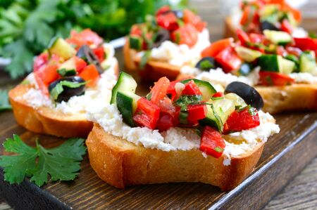 Delicious bruschettas with goat cheese and fresh vegetables. Crispy baguette slices with feta, tomatoes, cucumbers, peppers, olives, herbs. Healthy breakfast.