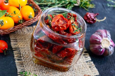 Sun-dried tomatoes with herbs, garlic in olive oil in a glass jar. 版權商用圖片