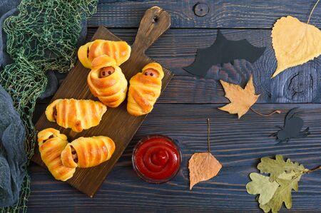 Lustige Wurstmumien im Teig mit Ketchup auf dem Tisch. Halloween-Essen. Ansicht von oben. Flach legen
