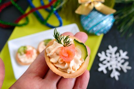 Tartlets with cream cheese and red salted salmon on a white plate for the festive table. Tasty portion light snack for a party. Finger Food. The top view, flat lay.