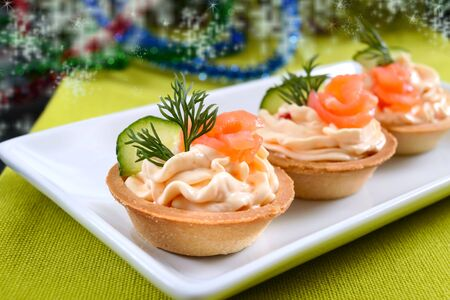 Tartlets with cream cheese and red salted salmon on a white plate for the festive table. Tasty portion light snack for a party. Finger Food.