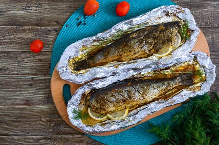 Baked herring with lemon and spices in foil on a wooden table. Tasty fish dish. Top view.