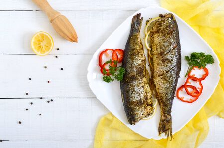 Baked herring with lemon and spices on the plate on a white wooden table. Tasty fish dish. Top view.