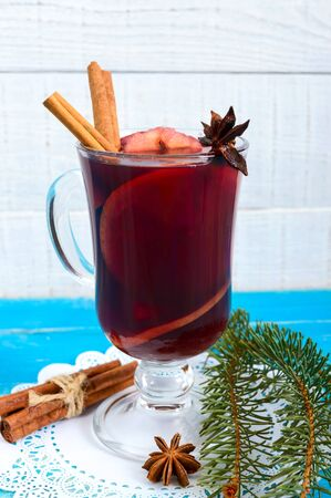 Christmas mulled red wine with spices and fruits on a blue wooden rustic table. Traditional hot drink with cinnamon, cardamom, oranges and anise at Christmas time. Vertical view.